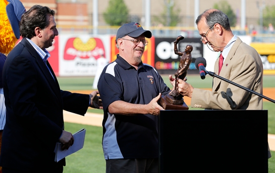 "Slug: SPT Hens30p  THE BLADE/JEREMY WADSWORTH  Caption: Jim Weber, center, is the first broadcaster to be inducted into the International League Hall of Fame as International League president Randy Mobley, right, presents him with the ""Curtain Call"" statue custom designed for Hall of Fame inductees Thursday, 05/29/14, at Fifth Third Field in Toledo, Ohio. At left is Mud Hens general manager Joe Napoli."